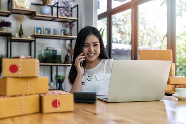 Une femme reçoit des commandes via son téléphone portable.