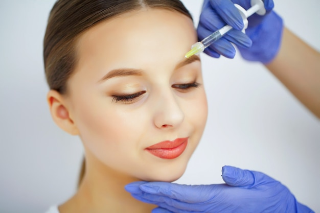 Une femme reçoit une injection sur son visage.
