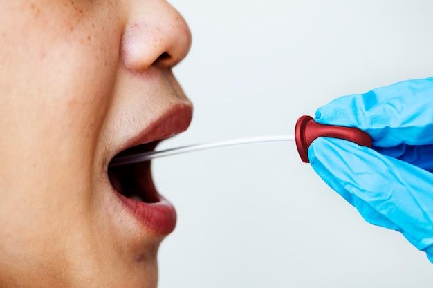Une femme reçoit un prélèvement buccal pour tester le coronavirus