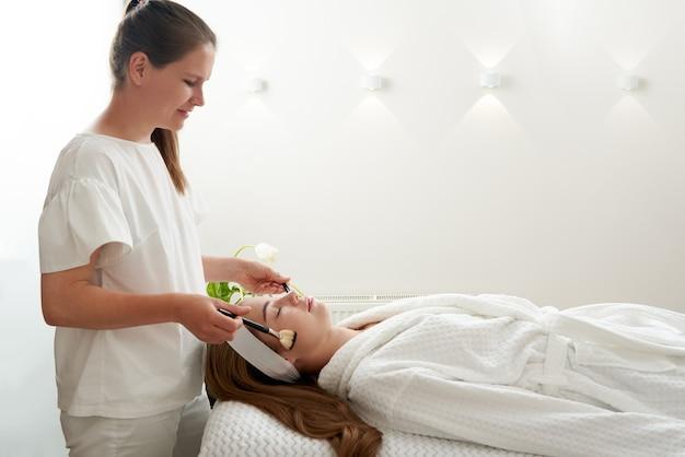 Une femme reçoit un traitement de brosses dans un concept de soins de la peau du visage d'une clinique de beauté se relaxant dans un salon de spa