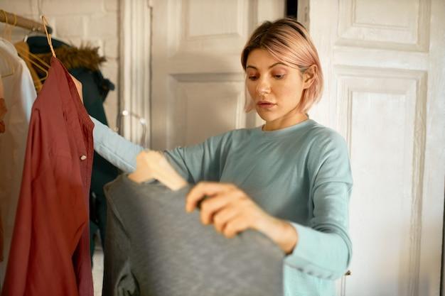 ¡femme reçoit des vêtements du centre de machine à laver.