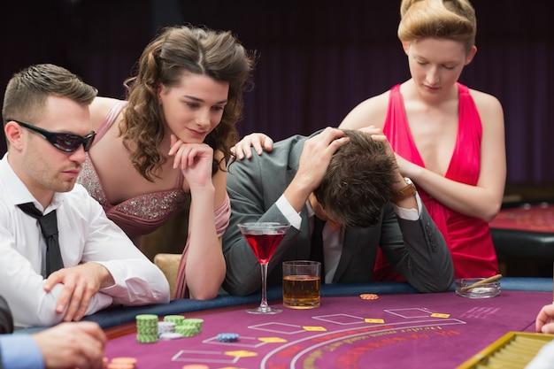 Femme réconfortant perdant au poker