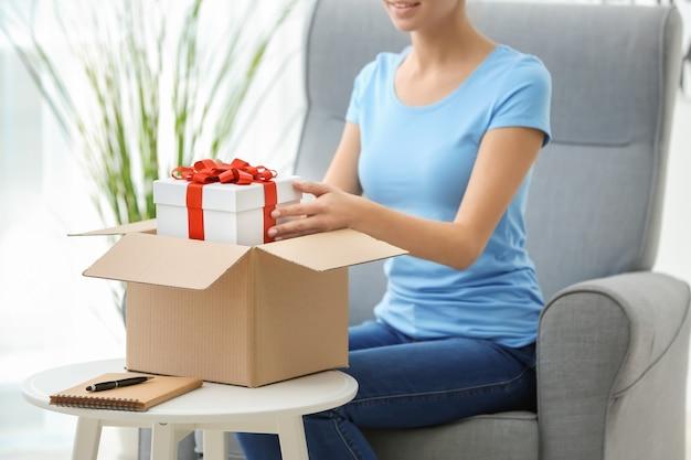 Une femme a reçu un cadeau dans une boîte à colis à la maison