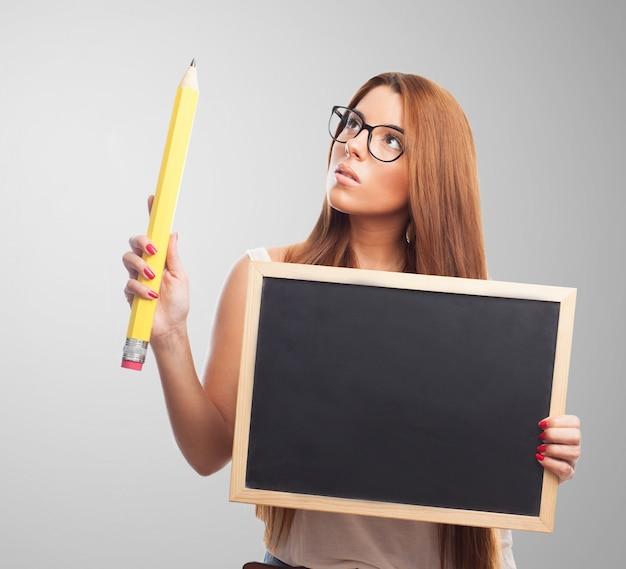 Femme réfléchi à lunettes tenant tableau noir et un grand crayon