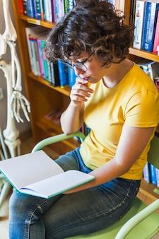 Femme réfléchie assis et lisant un livre dans la bibliothèque