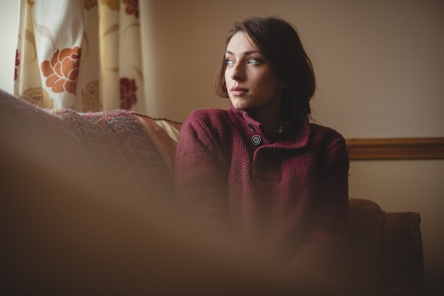 Femme réfléchie assise sur un canapé dans le salon