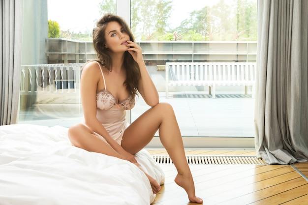 Femme réfléchie assise sur le lit