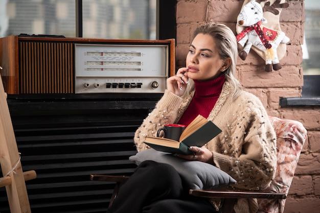 Femme réfléchie assise avec un livre et boire du café