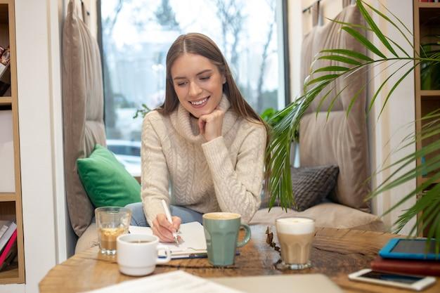 Une femme réfléchie, buvant beaucoup de café tout en faisant un travail créatif