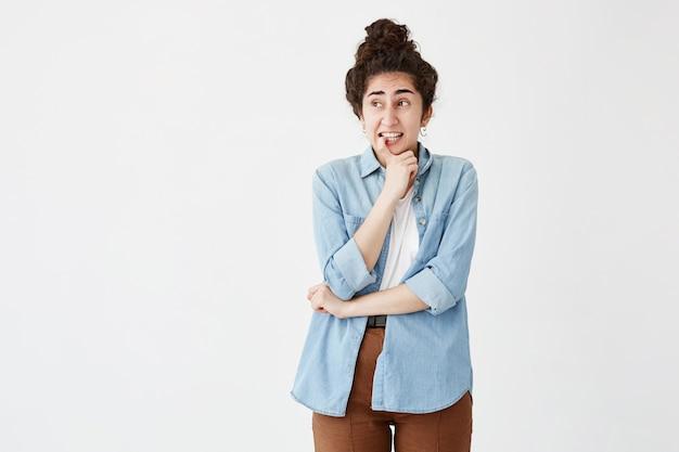 Femme réfléchie avec chignon, serre les dents blanches, garde le doigt sur les lèvres, regarde avec une expression pensive, en chemise en jean et pantalon marron. clueess jeune femme regarde de côté dans les doutes
