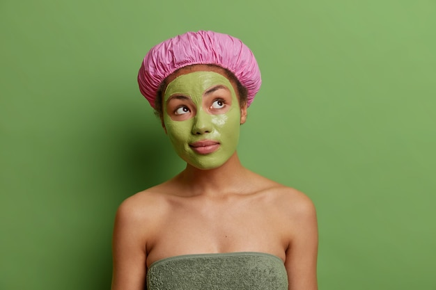 Une femme réfléchie concentrée au-dessus porte un masque facial vert sur le visage pour le rajeunissement porte une serviette de chapeau de bain autour du corps pense à la beauté de sa peau bénéficie des traitements de soins de la peau