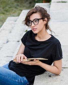 Femme réfléchie dans les escaliers tenant le livre