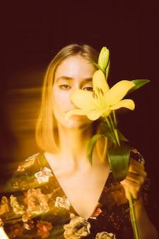 Femme réfléchie avec fleur jaune