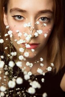 Femme réfléchie avec des fleurs blanches