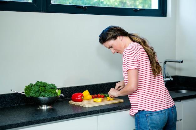 Femme réfléchie prépare des légumes pour le dîner sur une planche à découper en bois