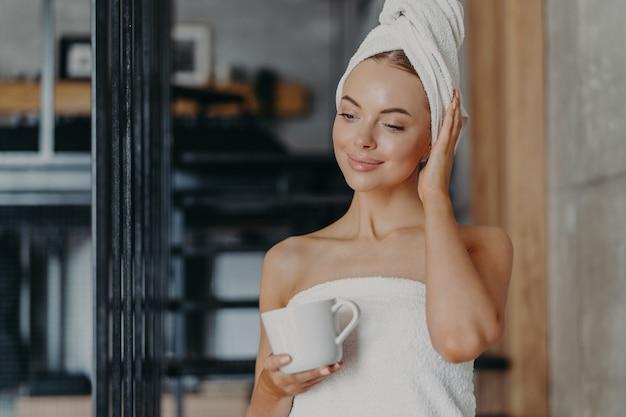 Femme réfléchie saine avec une peau saine et lisse boit du thé chaud concentré vers le bas