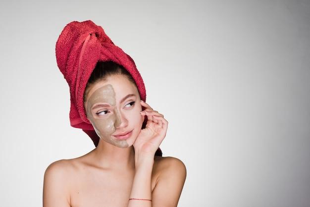 Une femme réfléchie avec une serviette sur la tête a appliqué un masque sur son visage