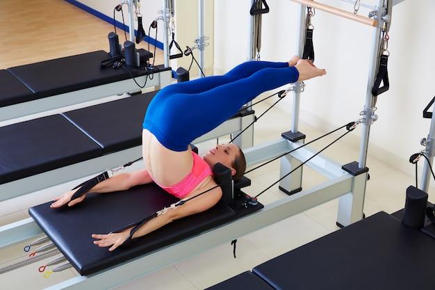 Femme réformatrice pilates over head exercice