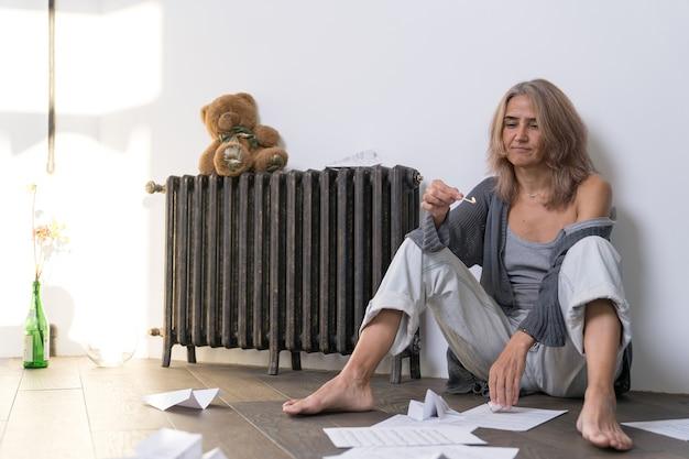 Une femme avec un regard détaché est assise sur le sol de son appartement avec une allumette allumée à la main