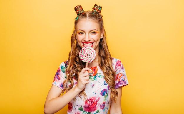 Femme avec un regard ludique lécher des bonbons avec la langue
