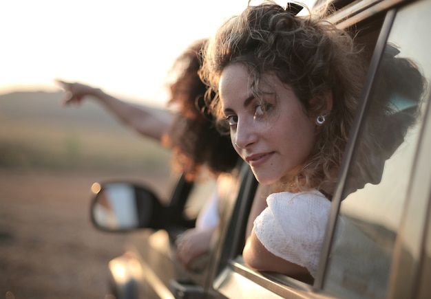 Femme regardant en arrière par la fenêtre de la voiture derrière une autre pointant son doigt