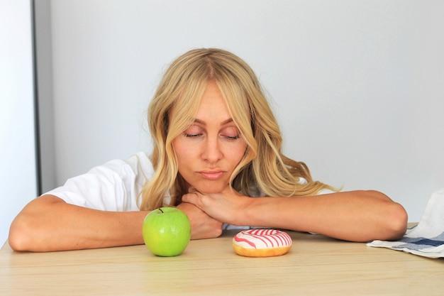 Femme regardant un beignet sur sa table, résistant à la tentation.