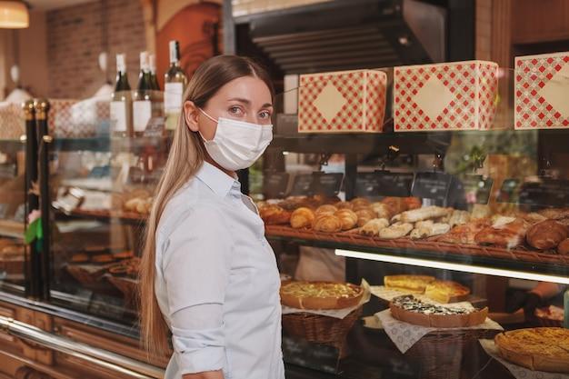 Femme regardant la caméra, faire du shopping à la boulangerie, portant un masque médical, copiez l'espace
