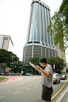 Femme regardant une carte avec un bâtiment géant derrière