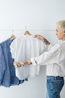 Femme regardant une chemise blanche