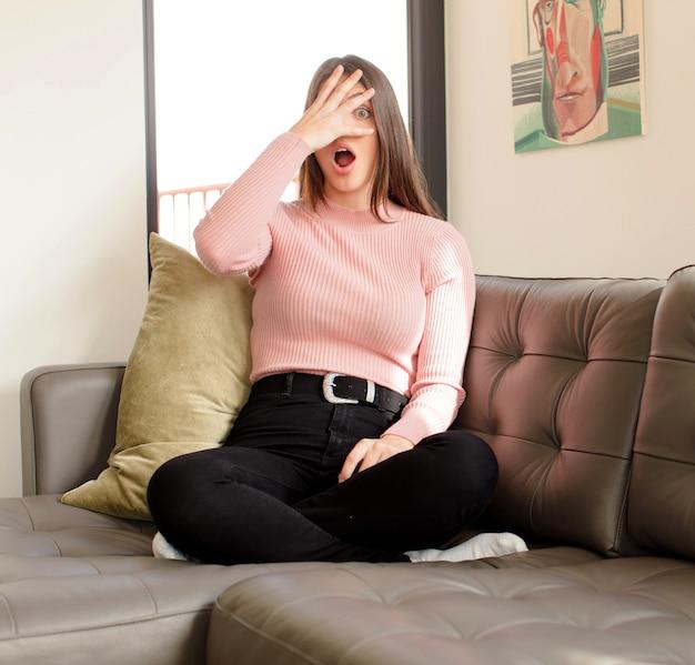 Femme regardant choqué, effrayé ou terrifié, couvrant le visage avec la main et furtivement entre les doigts