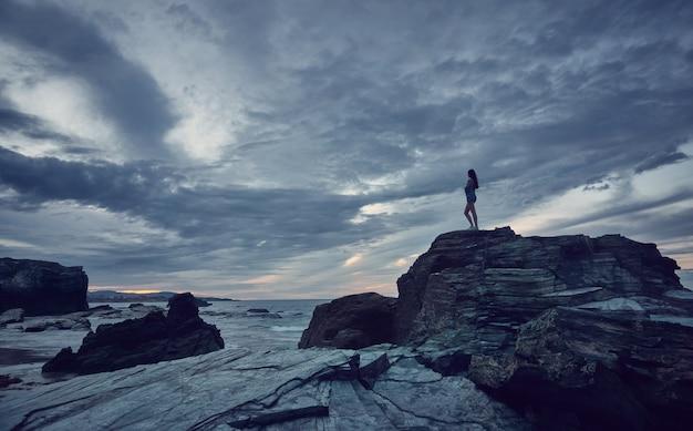 Femme regardant le coucher du soleil sur la plage. plage de catedrales sur la côte de galice