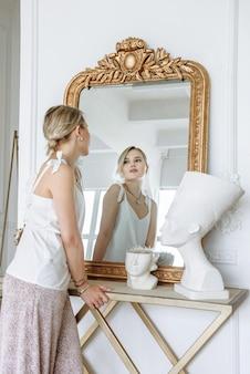 Femme regardant dans le miroir dans de nouveaux vêtements