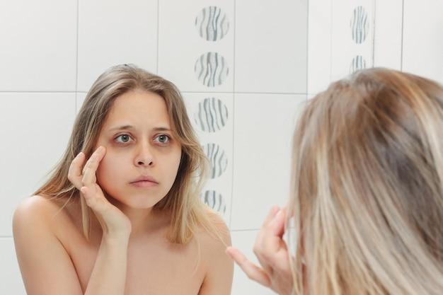 Femme regardant dans le miroir de la salle de bain à ses yeux