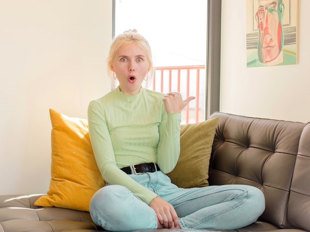 Femme regardant étonné d'incrédulité, pointant sur l'objet sur le côté et disant wow, incroyable