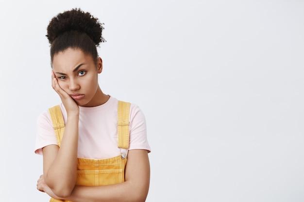 Femme regardant avec une expression indifférente et ennuyée, s'appuyant sur la paume, fronçant les sourcils et faisant la moue, fatiguée et agacée sur un mur gris