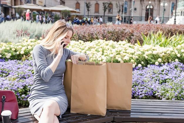 Femme regardant à l'intérieur du sac à provisions en parlant au téléphone portable