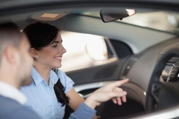 Femme regardant l'intérieur d'une voiture