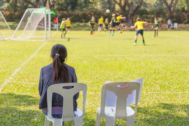 Femme regardant un jeu de football garçon école sur une journée ensoleillée