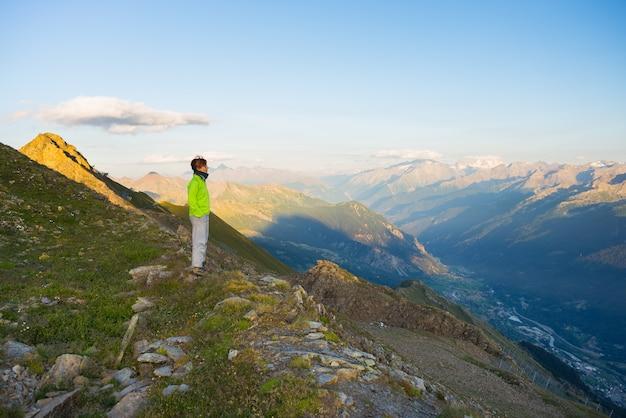 Femme regardant le lever du soleil sur les alpes