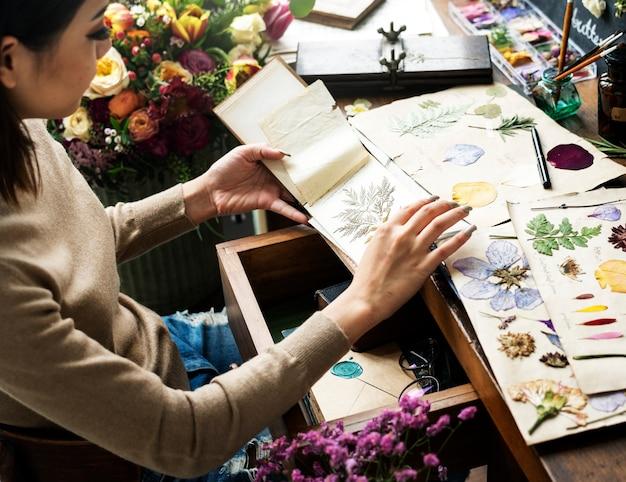 Femme regardant un livre de fleurs séchées