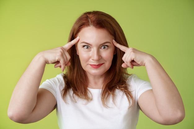 Femme regardant de manière ludique drôle contrôler votre esprit rousse idiote moyenne femme toucher les tempes yeux éclatants sourire ravi lire pensées essayer de deviner intrigué ce que penser mur vert