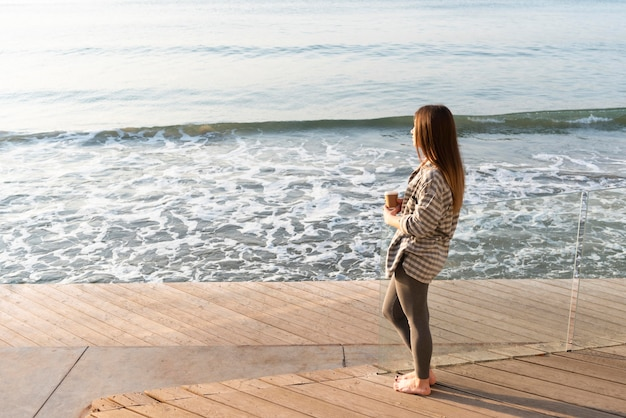 Femme regardant la mer avec espace copie