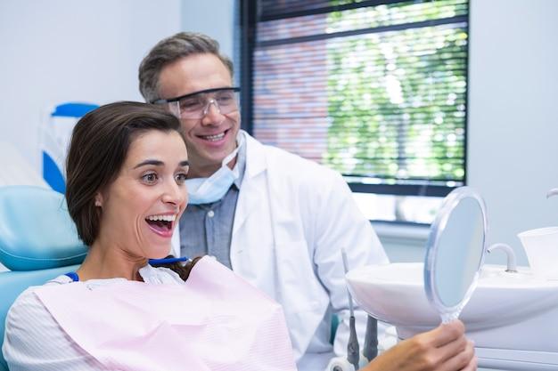 Femme regardant miroir par dentiste à la clinique médicale