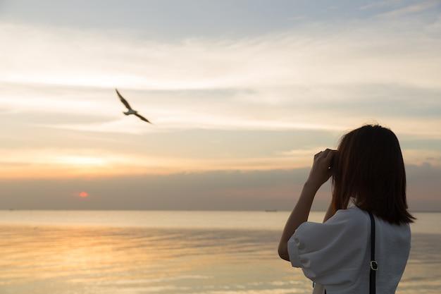 Femme regardant l'observation des oiseaux au bord de la mer.