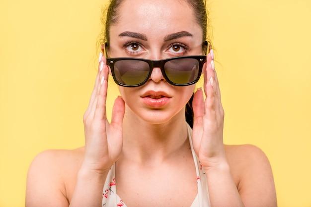 Femme regardant par-dessus de grandes lunettes de soleil