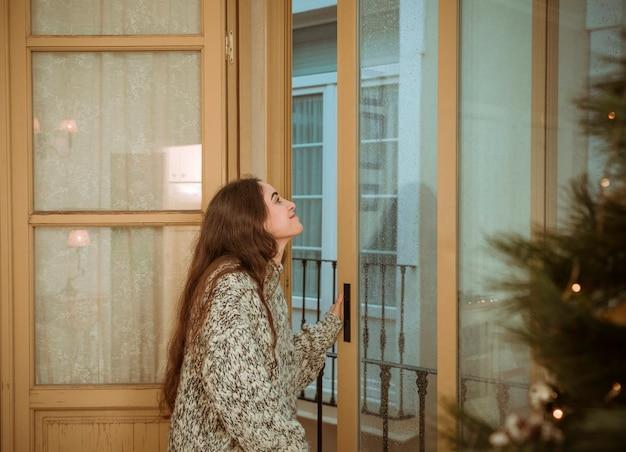 Femme regardant par la fenêtre à côté d'un arbre de noël
