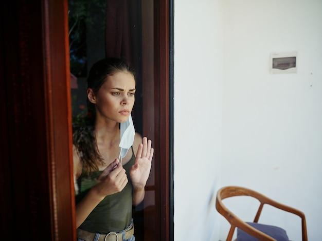 Femme regardant par la fenêtre portant un trouble de verrouillage de masque médical