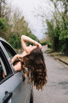 Femme regardant par la fenêtre de la voiture ouverte