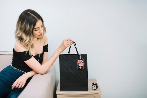 Femme regardant sac de vendredi noir avec des achats