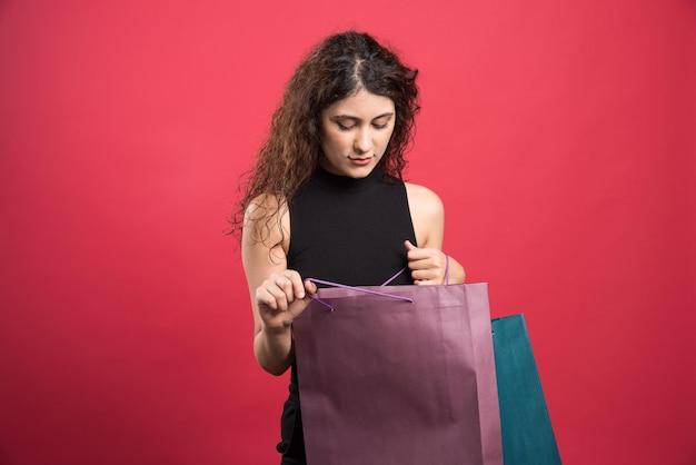 Femme regardant l'un des sacs sur rouge.